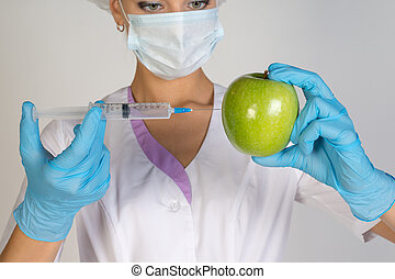 Woman holding an apple and is injected with a syringe....