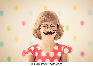 Funny kid with fake mustache Happy child playing in home