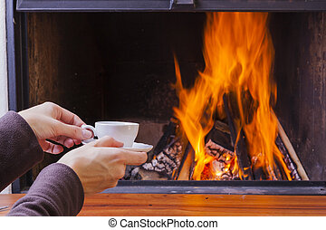 warming hands at fireplace with coffe and tea