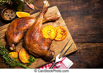 Roasted goose legs with oranges and spices. Cooking at...