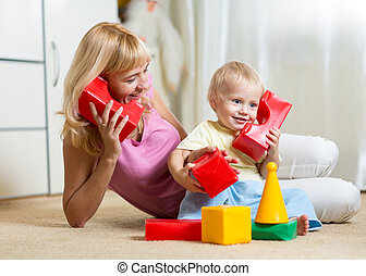 cute mother and kid boy playing together indoor - cute...