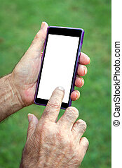 Hand senior man using Cell phone in grass background. He is...