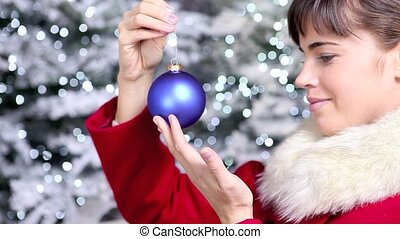 Christmas woman with blue ball of tree, smiling