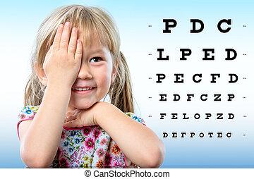 Cute little girl reviewing eyesight on chart.
