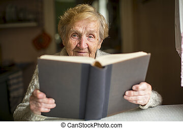 Elderly woman reading old book