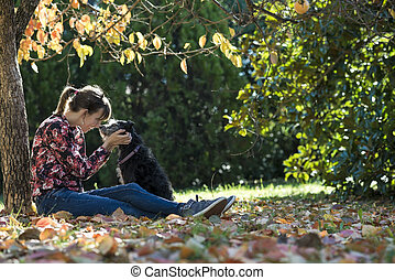 Young woman sitting under a coulourful autum tree lovingly...
