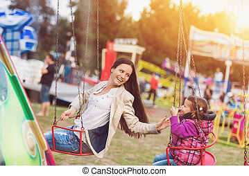 Mother and daughter at fun fair - Cute little girl with her...