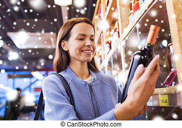 happy woman choosing and buying wine in market - sale,...