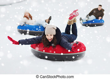 group of happy friends sliding down on snow tubes - winter,...