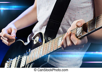 musician playing electric guitar with mediator - music,...