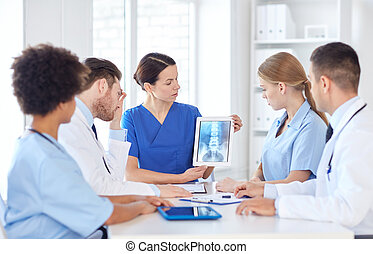 group of doctors with x-ray on tablet pc at clinic -...