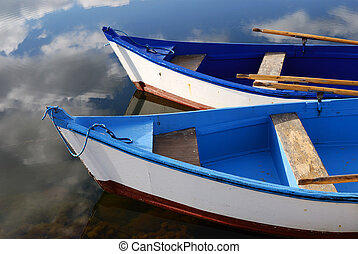 Small white and blue wooden boats - Sky reflection and...