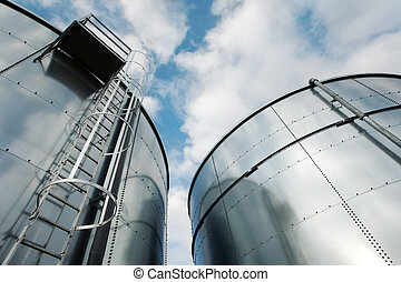 Refinery ladder and tanks - Low-angle shot of ladder and...