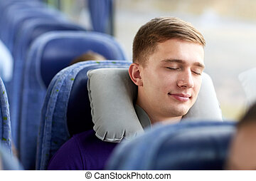 happy young man sleeping in travel bus with pillow -...