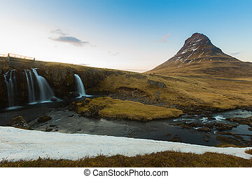 Kirkjufell volcanic mountain and waterfalls during late...