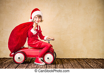 Christmas holiday concept - Child riding in red car. Kid...