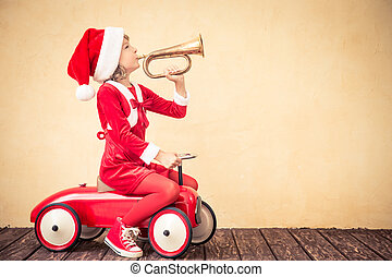 Christmas holiday concept - Child riding in red Christmas...