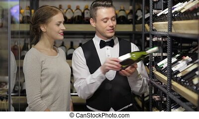 Confident male sommelier showing wine bottle - I recommend...
