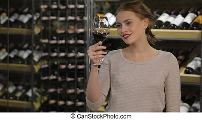 Attractive woman looking at the color of the wine in the...