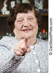 Senior woman pointing to you - Cheerful senior woman...