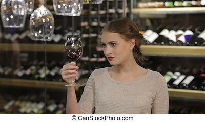 Beautiful young woman tasting red wine in a wine cellar....
