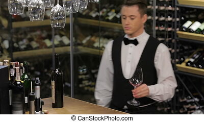 Sommelier examining wine. Image of confident male sommelier...