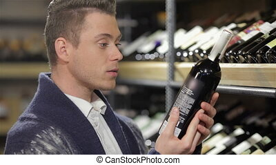 This is perfect wine. Handsome young man holding bottle of...