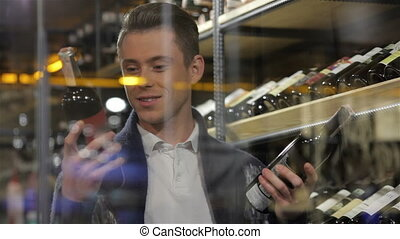 Man in a comparing two wines bottles. Sale, shopping,...