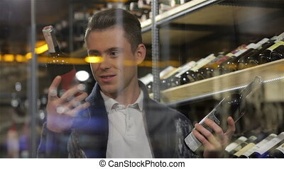 Man in a supermarket comparing two wines