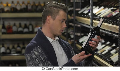 Man in a supermarket choosing the right wine Sale, shopping,...