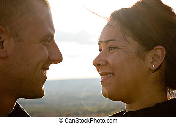 Young Romantic Couple - A young happy couple gazing into...