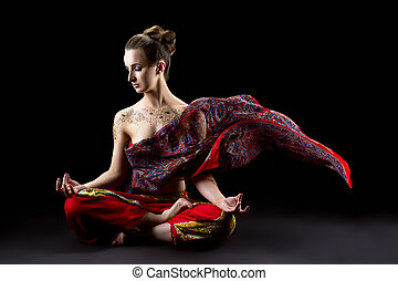 Beautiful calm woman meditates in lotus position and her...