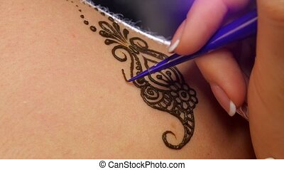 Accurate process of applying mehendi on the female back -...