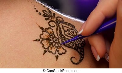 Art of mehendi Master works on models back, close up, light...