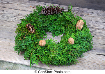 Christmas wreath with pinecones and walnuts on wooden table...