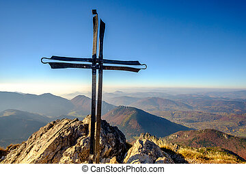 Scenic landscape view of mountain peak with metal cross,...