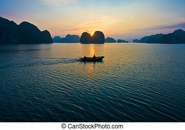 Sunrise at Ha Long Bay - Small fishermans boat approaches to...