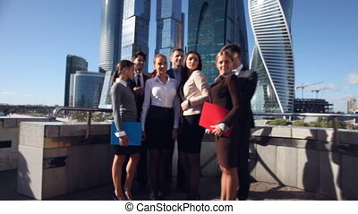 Business team outside office on skyscrapers background