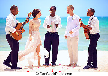happy wedding couple with musicians dancing on tropical...