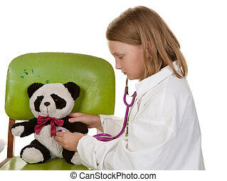 girl playing doctor with her toys - young girl playing...