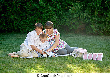 family sitting on the grass in a park with letters love and read book
