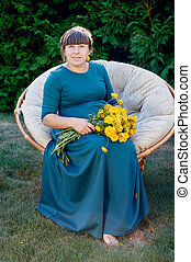 Pregnant woman sitting on a chair with a bouquet of flowers...