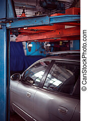 Auto at mechanic shop - Picture showing grey car parked at...