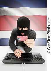 Hacker with flag on background holding ID card in hand - Costa Rica