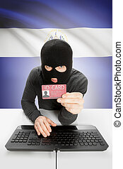 Hacker with flag on background holding ID card in hand - El...