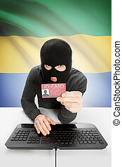 Hacker with flag on background holding ID card in hand -...