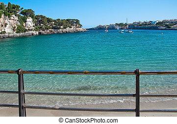 Beach in Porto Cristo with turquoise water and blue sky on a...