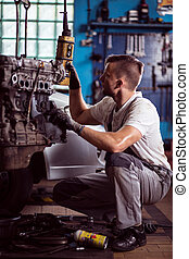 Engine check up - Mechanic is lifting engine for better...
