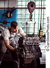 Petrol engine check up - Picture showing mechanic examining...
