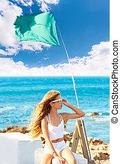 Blond kid teen girl on the beach long curly wind hair